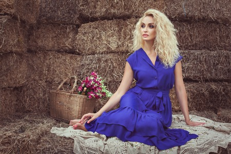 footsie: Beautiful blonde woman in the hayloft in the village, she is dreaming and waiting. Stock Photo