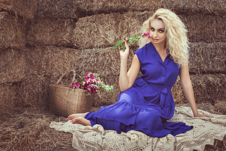 footsie: Beautiful blonde woman in the hayloft in the village, she flirts holding a flower. Stock Photo