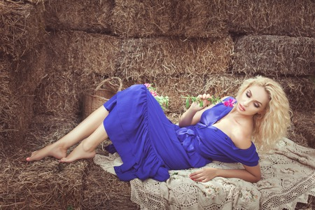 Beautiful woman lying in the hay, she caresses herself wildflowers.