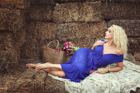expects: Blonde woman lying on hayloft near a basket with flowers. She expects a man. Stock Photo