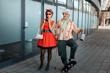 he old: Old man saunters with a young girl, he rides a skateboard. Stock Photo