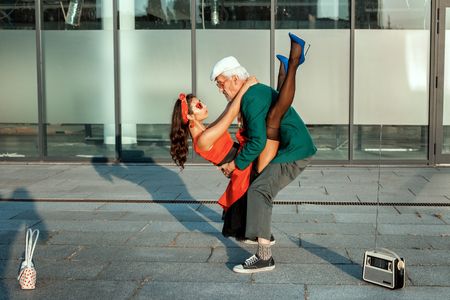 humorously: Old man dancing with a young girl in retro style.