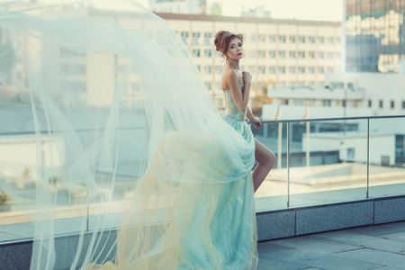 flyaway: Young girl standing on the balcony, her dress fluttering in the wind.
