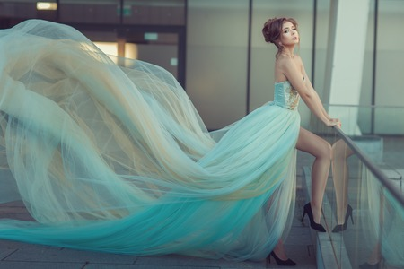 Young girl's dress gently blue color, it flying in the wind.