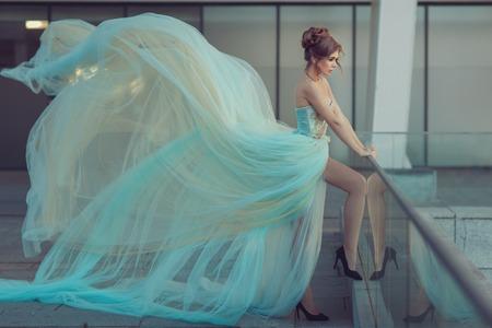 flyaway: Beautiful girl standing on the balcony, she was wearing a gentle blue dress that develops in the wind, a very long dress. Stock Photo