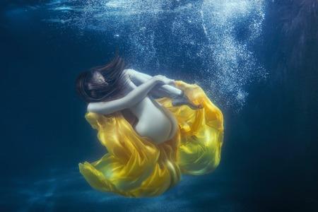 Womens dress develops under water, it fantastically dives. Stock Photo
