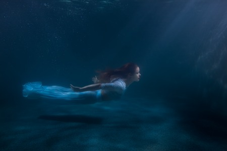 Woman as the mermaid swims under water, she in a white dress.