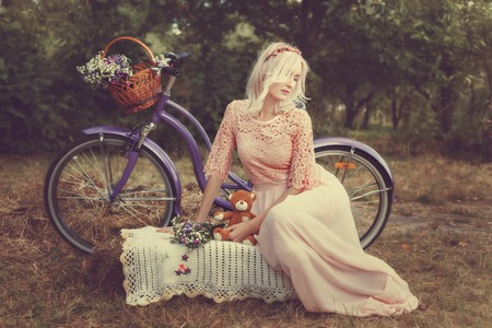 Sad girl in a park with a childrens toy, near the bike. Stock Photo