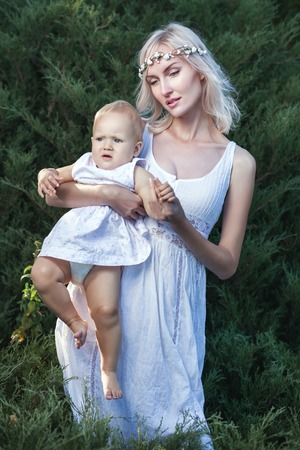 godlike: The girl in a white dress holding a baby in her arms.