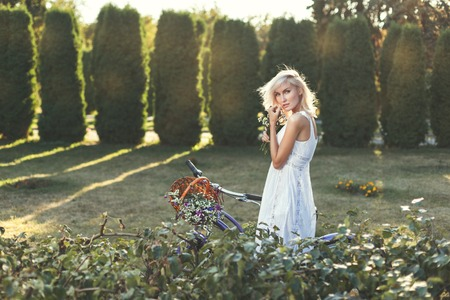 Modest girl in a white dress walks in the park. Stock Photo