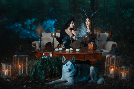 diabolic: Girls of the witch in the wood cook a magical potion, the wolf lies nearby.