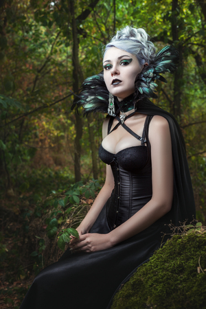 Portrait of gothic girl in the woods, wearing her corset and collar of feathers. Stock Photo