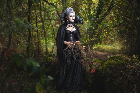 Scary girl witch in black clothes walking in the woods and collect dry grass.