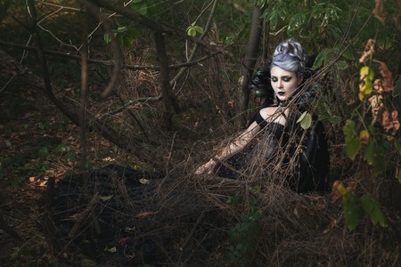 diabolic: Gothic girl in black clothes is sleeping in the woods.