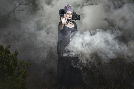 diabolic: Gothic girl in black clothes stands in the smoke.