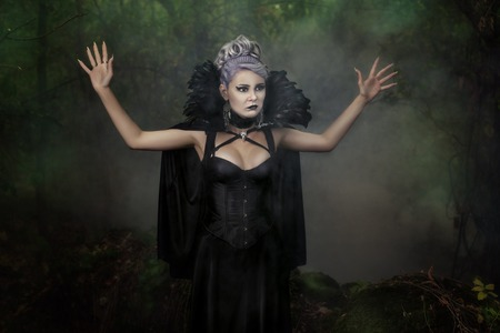 Gothic girl raised her hand threateningly up, it's scary.