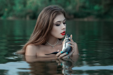 The woman is in water and talks to fish, holding her in hand.