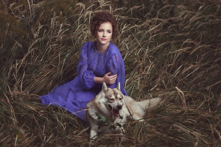 huskies: The curly-headed girl dressed in a beautiful dress lies a dog huskies nearby. Stock Photo