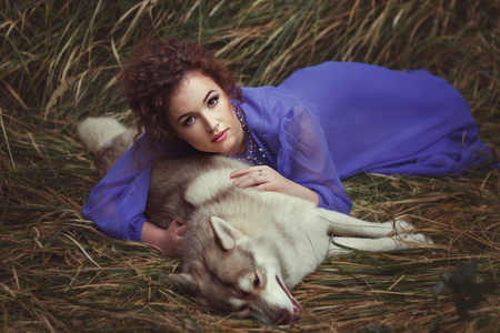 dearness: Girl lies on a dead dog, they are in a fairy tale. Stock Photo