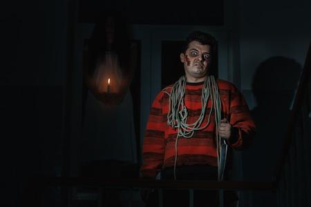 imminence: horrible hombre con un cuchillo de pie en la sala, una mujer es un fantasma detrás de él.