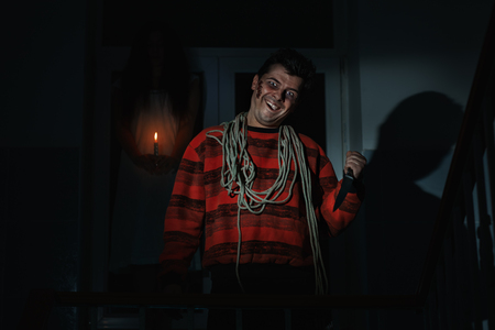 imminence: Terrible man smiling in his hands a knife and a rope noose around his neck.