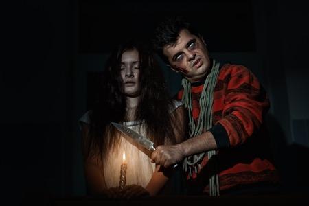 imminence: Terrible el hombre amenaza con un cuchillo a la mujer terrible. Foto de archivo