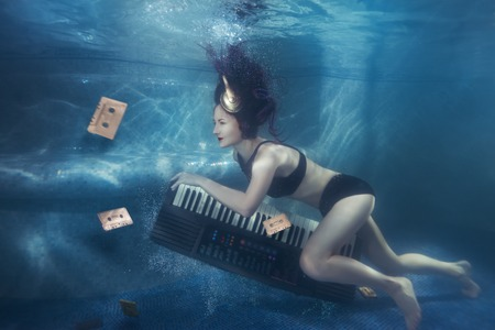 Girl with piano under water on her head headphone.