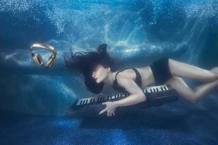 profound: Girl swims with piano under water in the pool. Stock Photo