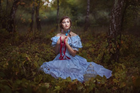 dreaminess: Young girl with red ribbon in hands sitting on the grass in the forest. Stock Photo