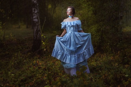snění: Girl in vintage dress in the forest at night.