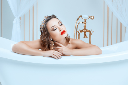 Portrait of a woman in a bath, she is a queen with a crown on his head.