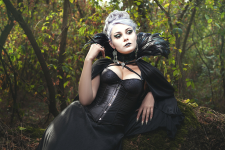 witchery: Beautiful woman a witch in the dark forest.