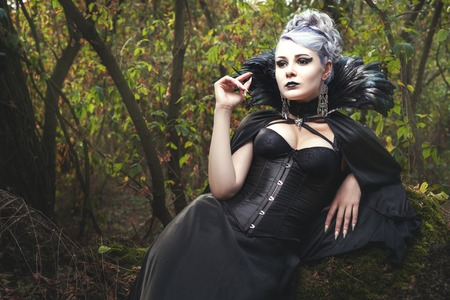 Beautiful young woman a witch, she was in the dark forest.