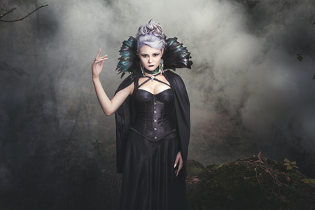 witchery: Beautiful woman conjures witch in the woods around the smoke.