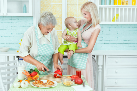 Mom plays with the baby in the kitchen while grandmother is preparing dinner.