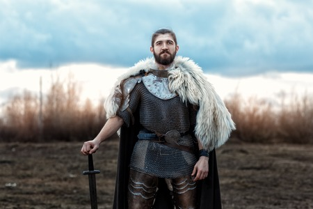 formidable: Formidable man warrior in armor and sword standing in a field and protects.