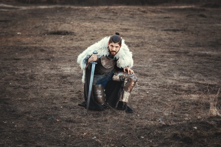 formidable: Formidable man with a sword, stood on one knee in the field.