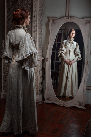 mirror: The woman looks in the mirror, retro image.