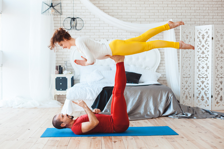 Man and woman practicing yoga, they trained at home. 写真素材