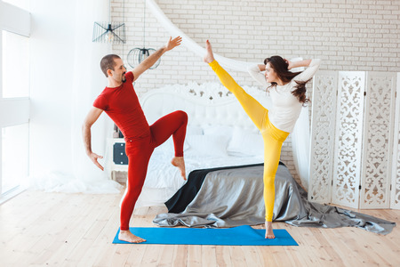 Man and a woman train in the morning, they do yoga.