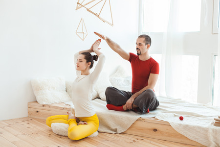 Man and a girl of yoga, they meditate in the morning on the bed. 写真素材