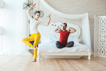 Sporty and healthy married couple is engaged in yoga.