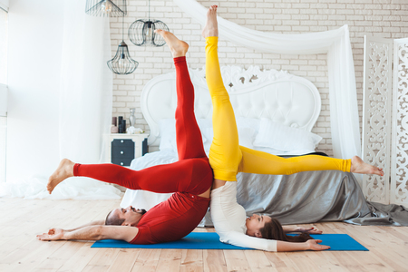 Sports stand on the head, a married couple is engaged in yoga in the morning. Stock Photo