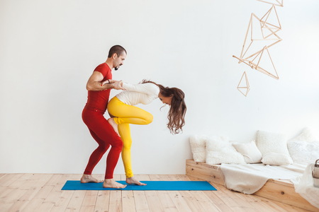 Man is training a woman in the morning gym, they are at home in the bedroom.