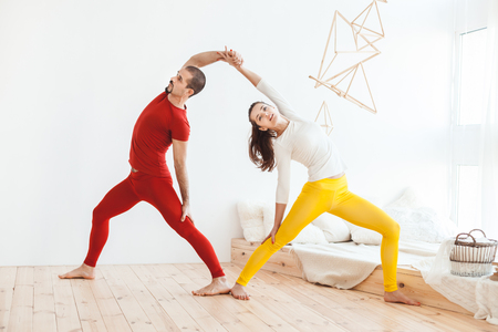 Young couple leads a healthy lifestyle, they do morning yoga gymnastics.