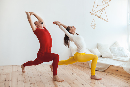 Woman and the man do sports bendings, these are morning exercises of the house. Stock Photo
