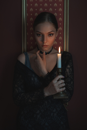 Beautiful and sad woman in a dark room with a candle.