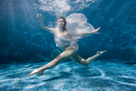 Woman dances underwater sports dance, her dress fluttering under the water.