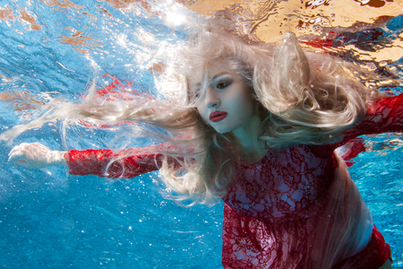 Surrealism is a blonde woman under the water, her hair is fluttering.