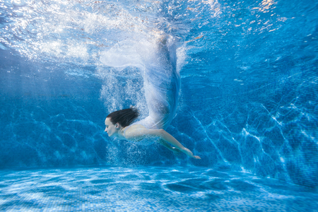 Woman mermaid dives under the water in the pool, she in a white dress and a lot of water splashes.